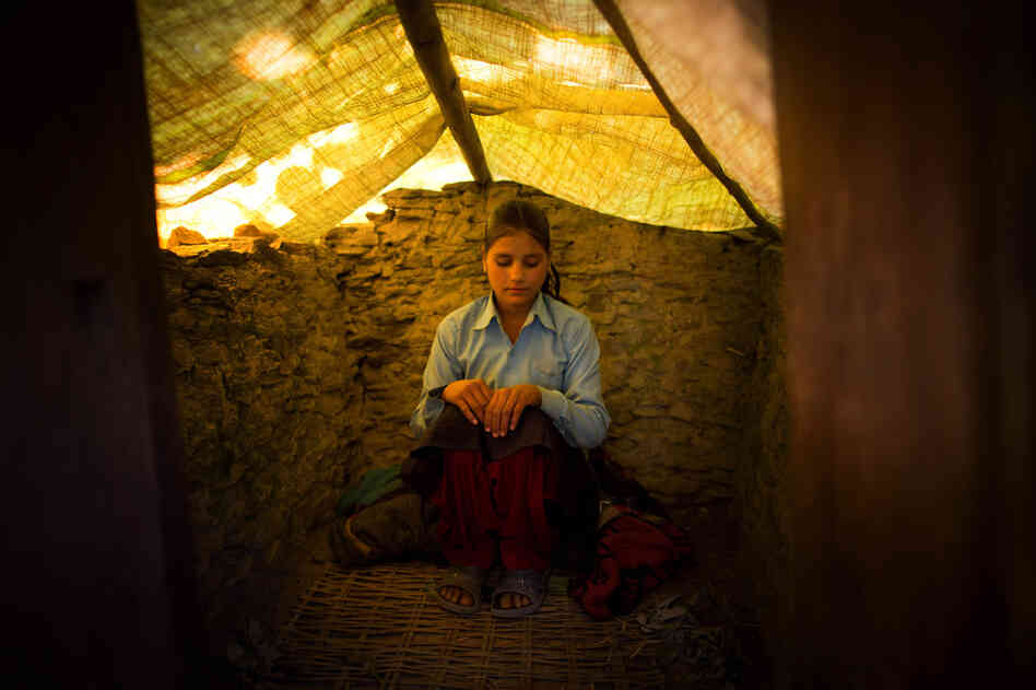 Jaukala, 14, poses for a photo in the family's chaupadi shelter, a squat shed measuring approximately 1 meter by 2 meters, in Rima village, Achham, Nepal. A tarp serves as a temporary roof to this structure, still under construction. Jaukala must sleep here while she has her period.