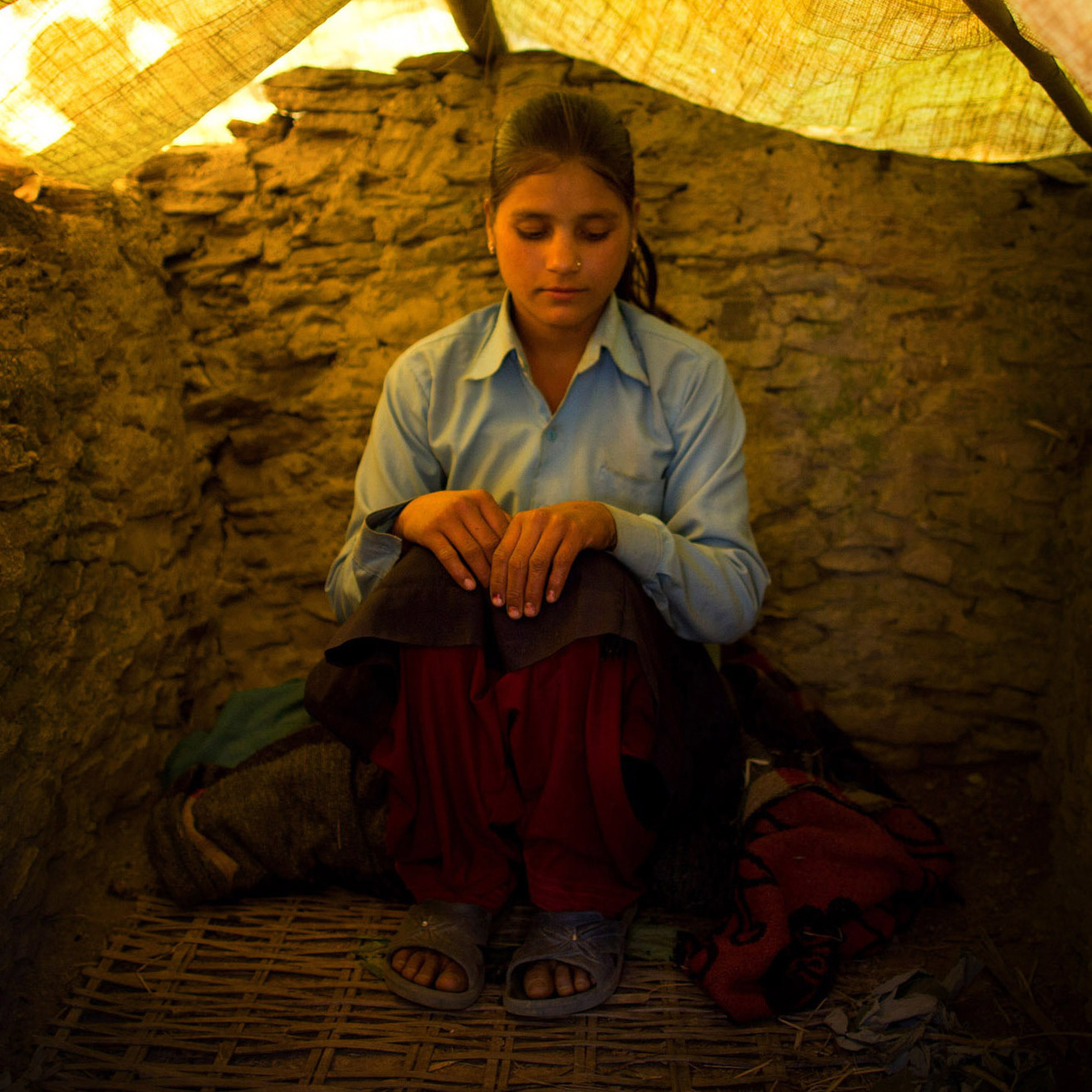 Wearing her school uniform, Jaukala, 14, poses for a photo in the family's chaupadi shelter, a squat shed measuring approximately 1 meter by 2 meters, in Rima village, Achham, Nepal. A tarp serves as a temporary roof to this structure, still under construction. Jaukala must sleep here while she has her period.