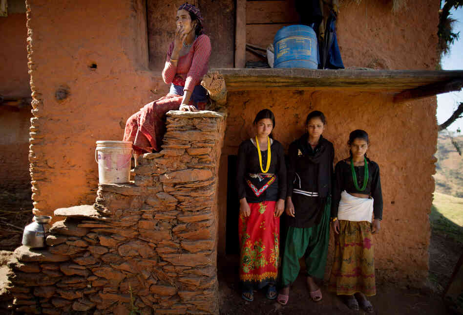 Tulachi, 15, Jandhara, 15, and Amana, 14, pose for a photo in front of the entrance to a crawlspace under their home, which serves as their extended family's chaupadi shelter, in Rima village. They share the space with the household's herd of goats.
