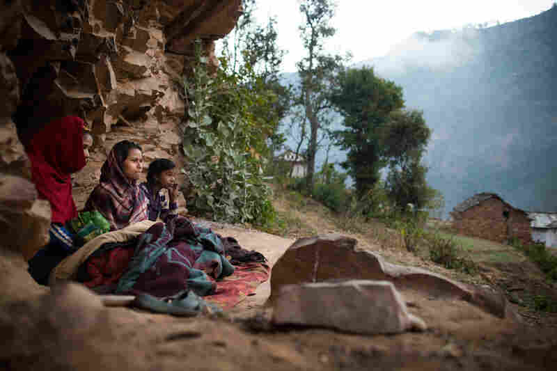 Young women observing chaupadi wake up under a rock outcropping in Kalekanda village, Achham, Nepal.