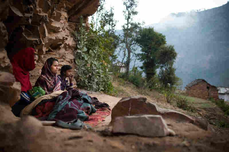 Young women observing chaupadi wake up under a rock outcropping in Kalekanda village, Achham, Nepal.