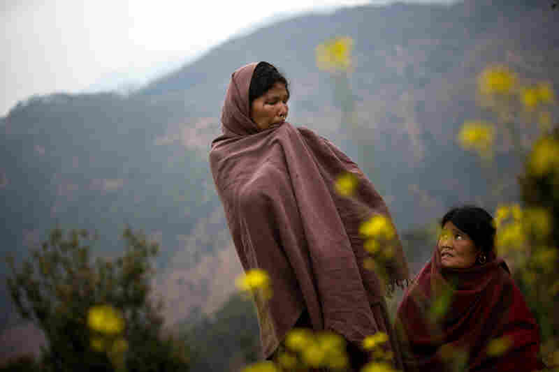 """Sauri (left) and her sister-in-law Birma stand in the spot where Sauri's 17-year-old daughter, Laxmi, recently burned to death while sleeping in a chaupadi shed in an area far from the family's home, near Dhakari village, Achham, Nepal. """"I have many daughters,"""" said Sauri, """"but she was the one who was always with me."""" The family has since destroyed the shed."""