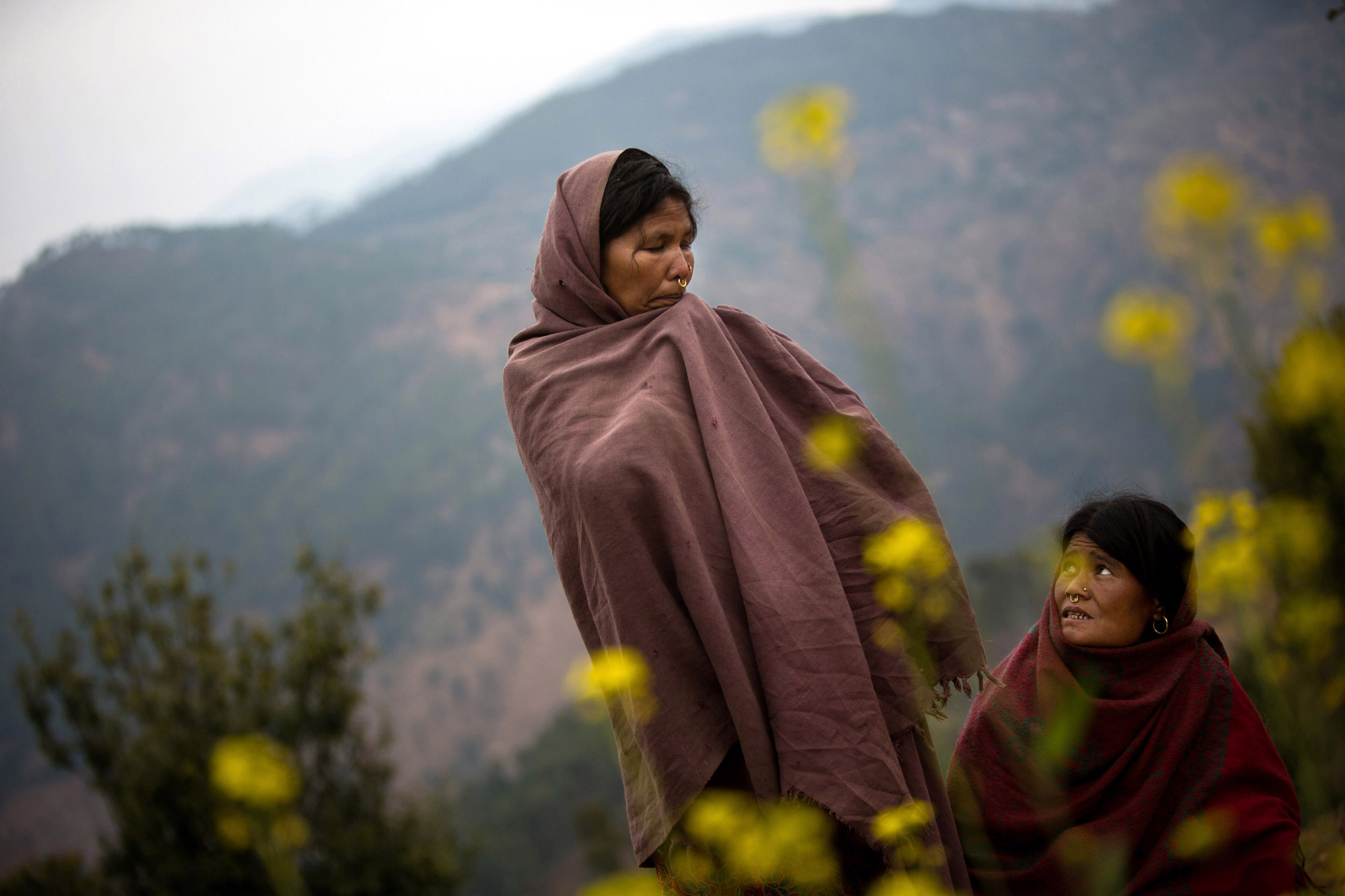 "Sauri (left) and her sister-in-law Birma stand in the spot where Sauri's 17-year-old daughter, Laxmi, recently burned to death while sleeping in a chaupadi shed in an area far from the family's home, near Dhakari village, Achham, Nepal. ""I have many daughters,"" said Sauri, ""but she was the one who was always with me."" The family has since destroyed the shed."