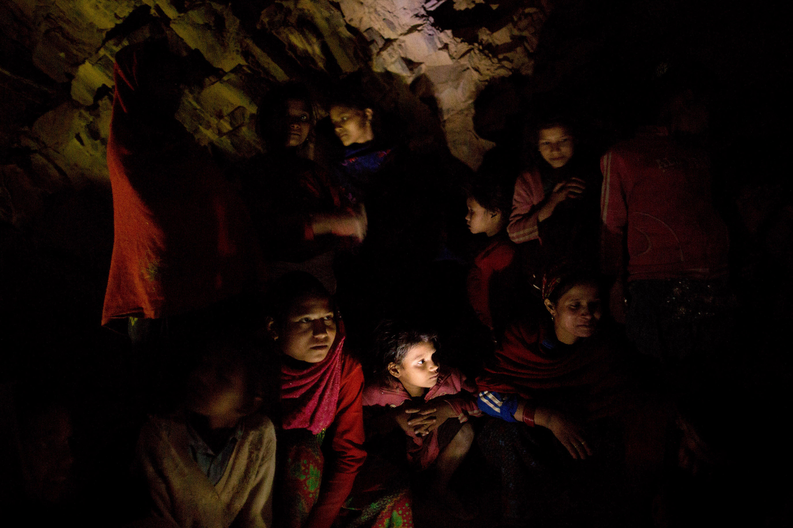 A group of women and girls chat around a fire as they prepare to sleep under a rock outcropping in observance of chaupadi in Kalekanda village. The space, shared by all of the village women, provides no protection from the elements.