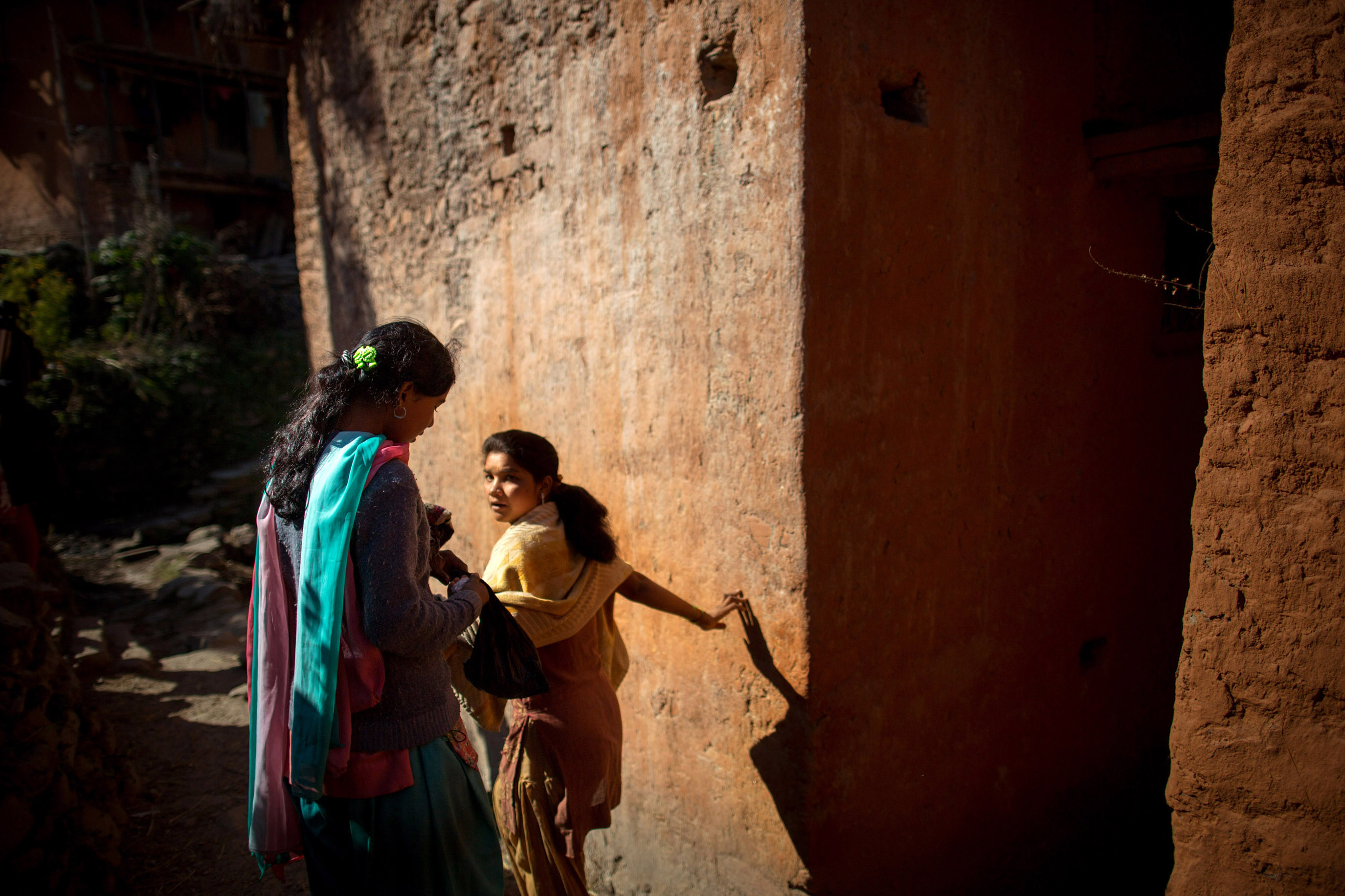 Radhika (left), 14, avoids touching others in her village as she takes a back path toward a water pump where girls practicing chaupadi are allowed to bathe, in Siddheshwar village, Achham, Nepal. During chaupadi, women may not use the regular village water sources, often walking long distances for obligatory daily washing.