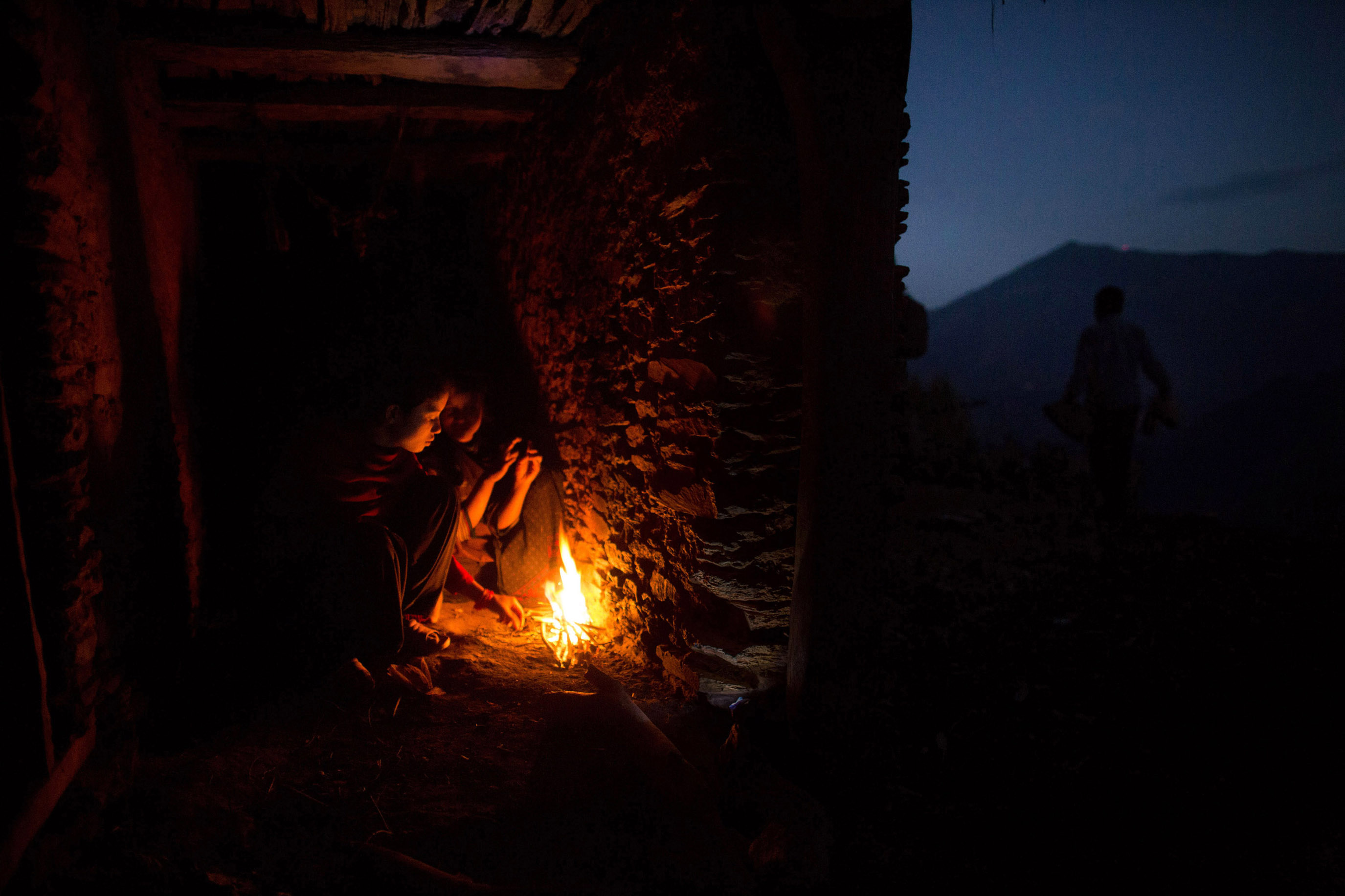 Nabina (left), 17, and Khadi, 12, huddle around a fire for warmth as they prepare to sleep in the household chaupadi shelter, a crawlspace with no door under the home shared with the family's animals.