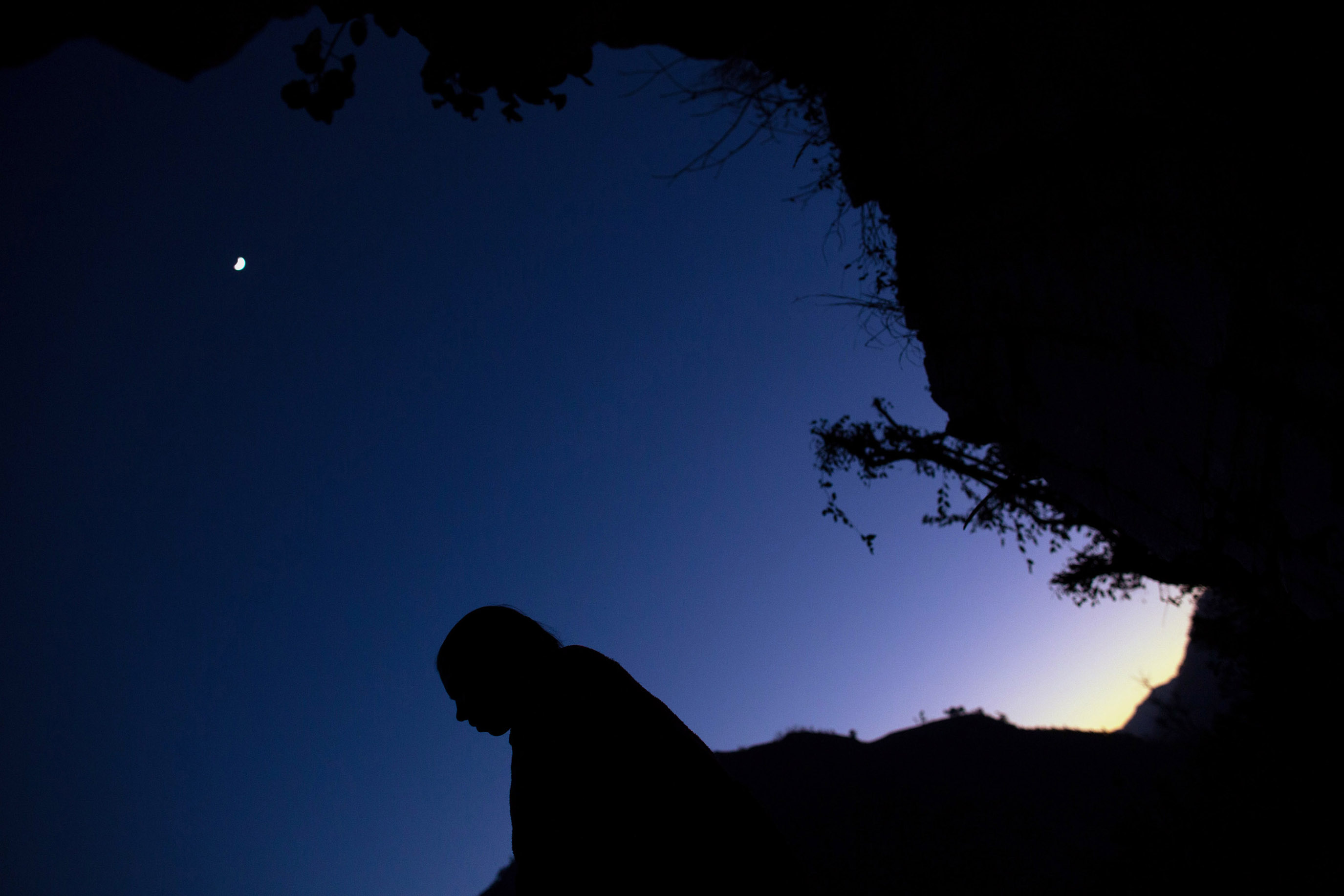 The moon glows overhead as Maisara, 15, prepares to sleep under a rock outcropping in observance of chaupadi in Kalekanda village.
