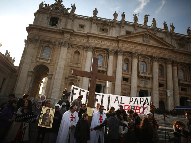 A church group prepares to pray for Pope Benedict XVI on the steps of St. Peter's Basilica on Tuesday.