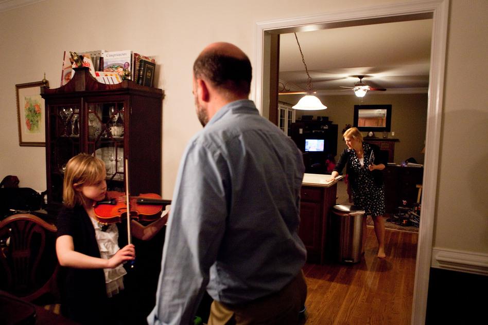 Anna, 8, practices the viola with her stepdad as her mother cleans up after dinner. All five of their daughters play an instrument and practice after dinner four nights a week.