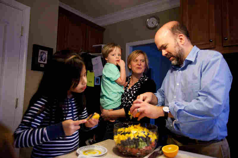 Celedonia, 8, Gavin, 3, Spencer and Brown gather around the kitchen as Brown prepares a fruit salad for dinner.