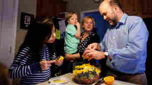 From left: 8-year-old Celedonia, 3-year-old Gavin, Amy Spencer and Doug Brown gather around the kitchen as Doug prepares a fruit salad for dinner.