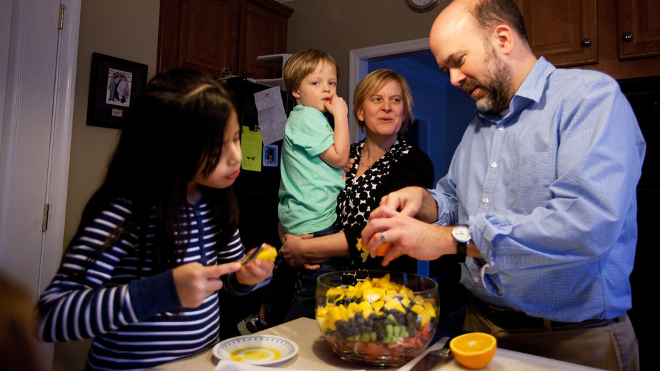 From left: 8-year-old Celedonia, 3-year-old Gavin, Amy Spencer and Doug Brown gather around the kitchen as Doug prepares a fruit salad for dinner. (NPR)