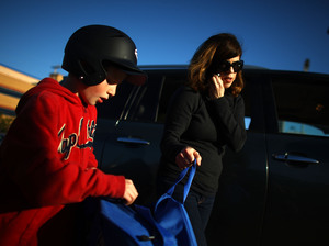 Yvonne Condes helps her son Alec get ready for baseball practice.