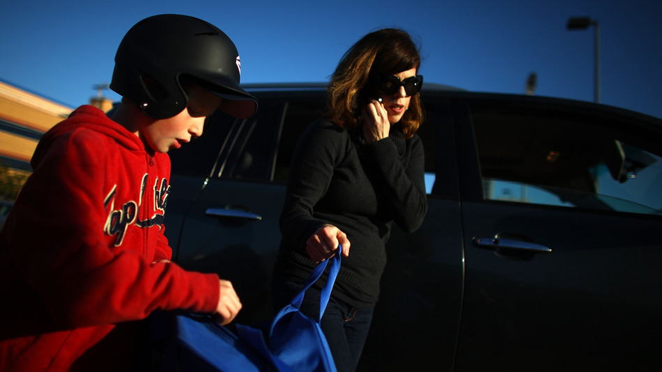 Yvonne Condes helps her son Alec get ready for baseball practice. (NPR)
