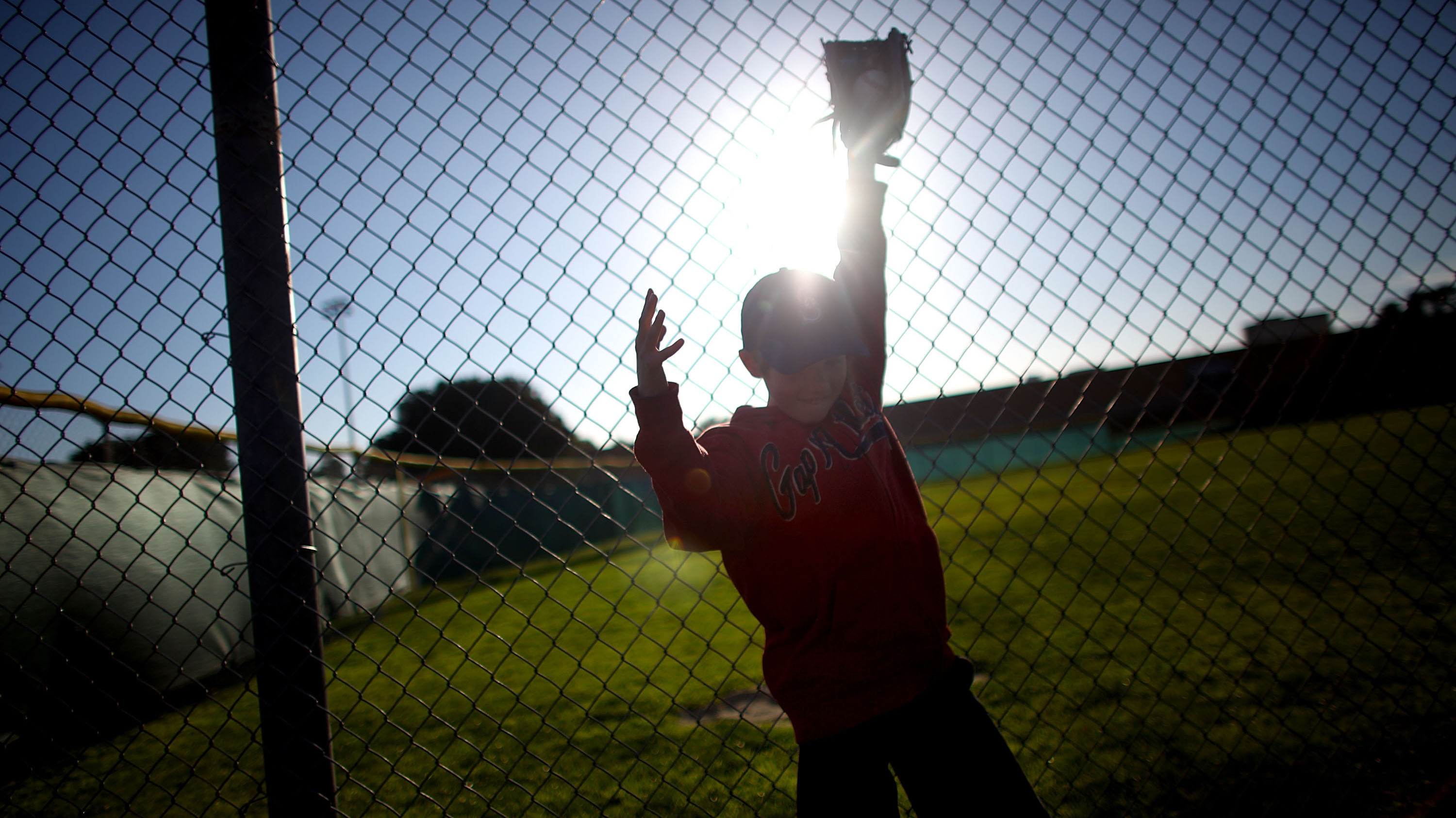 Alec Condes, 9, gets ready for baseball practice at a park in Los Angeles.