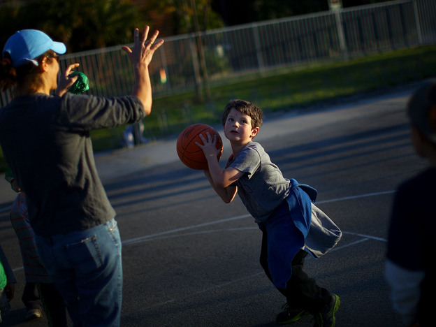 Henry Condes, 7, practices shooting a basketball. His mother, Yvonne, spends most afternoons ferrying her two boys from one sporting activity to another.