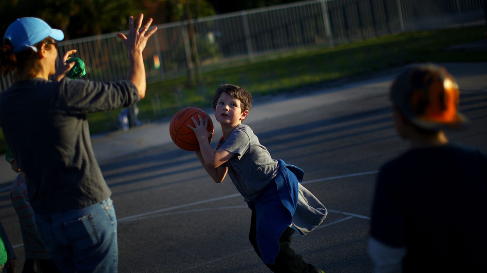 Henry Condes, 7, practices shooting a basketball. His mother, Yvonne, spends most afternoons ferrying her two boys from one sporting activity to another. (NPR)