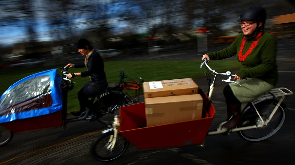 Emily Finch (left), a mother of six, and Martina Fahrner, co-owner of Clever Cycles in Portland, Ore., ride Bakfiets Cargobikes. Finch traded in her Chevy Suburban for her bicycle, which she uses for her daily errands. (NPR)