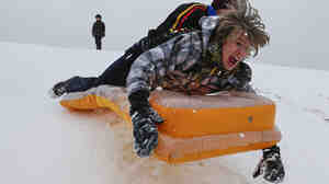 While severe winter weather has caused problems for many in the Great Plains, it has also provided some opportunities for fun. On Monday, Simon Mourning (front) and Chance Cain went sliding in Wichita, Kansas.
