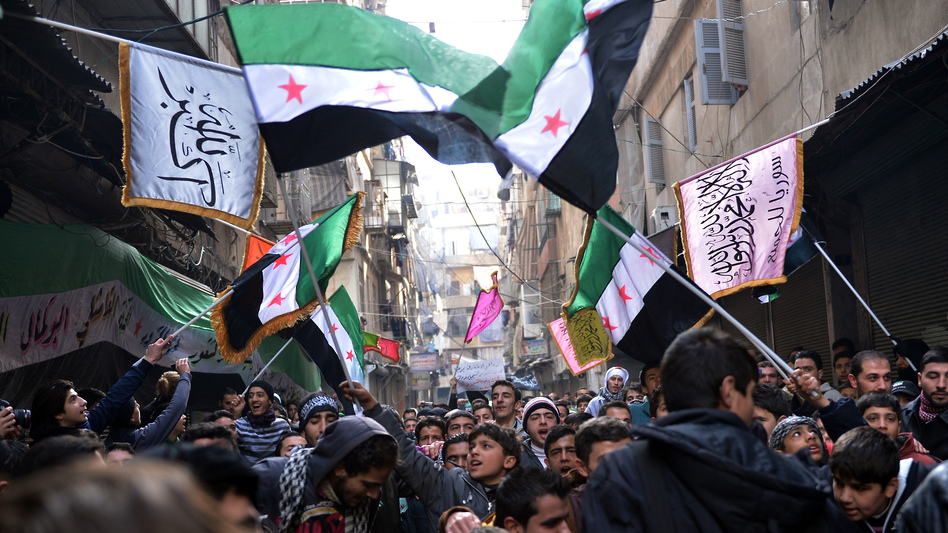 Secular demonstrators, shown at a protest march this month in Aleppo, wave the old Syrian flag (green, white, black and red) that has become the symbol of their opposition movement. (AFP/Getty Images)