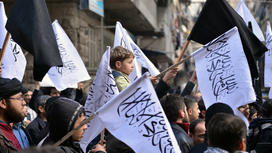 Supporters of the opposition Islamist group Al-Nusra wave their black-and-white flags during an anti-government demonstration earlier this month in the northern Syrian city of Aleppo. (AFP/Getty Images)