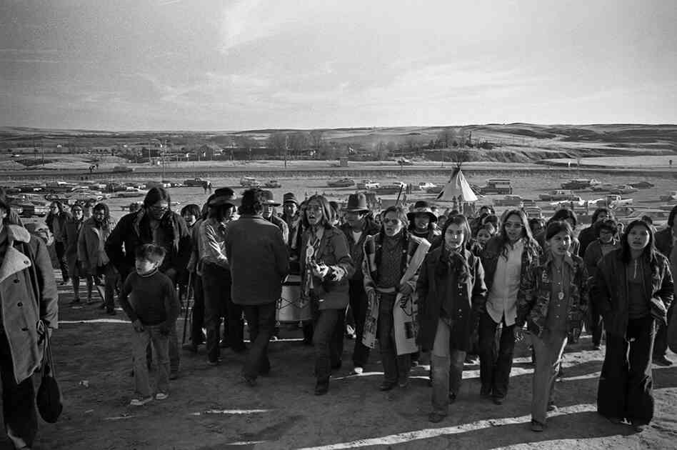 The drum leads the people to the mass grave of those who were killed in the 1890 massacre at Wounded Knee.