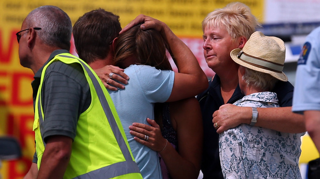People grieve outside New Zealand's Muriwai Surf Lifesaving Club after the fatal shark attack at Muriwai Beach on Wednesday. (Getty Images)