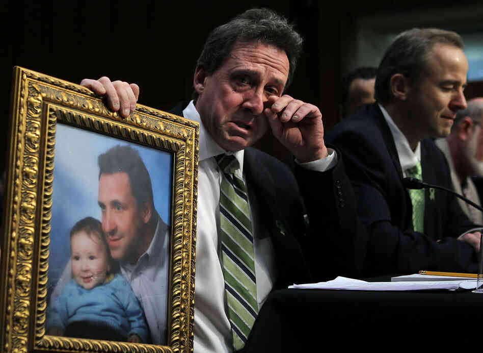 Neil Heslin, father of six-year-old Sandy Hook Elementary School shooting victim Jesse Lewis, holds a picture of him with Jesse as he testifies during a hearing before the Senate Judiciary Committee on Wednesday.