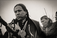 Crow Dog leads prayers and blessing for two warriors who had been wounded when they were shot in the legs.