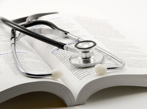 stethoscope on open book on a white background
