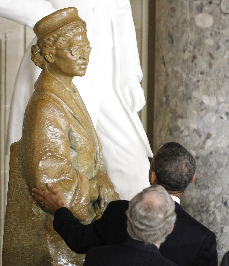President Obama reached out to touch the statue of civil rights icon Rosa Parks during Wednesday's dedication ceremony in the U.S. Capitol. Senate Minority Leader Mitch McConnell, R-Ky., was behind the president.