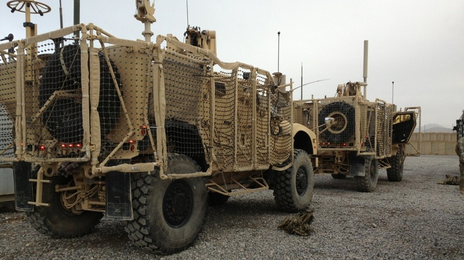 A pair of mine-resistant, ambush-protected vehicles are lined up for a convoy to Kandahar Airfield. One of the trucks broke down before leaving Forward Operating Base Frontenac. The unit has to move out 50 vehicles from the compound. (Sean Carberry/NPR)