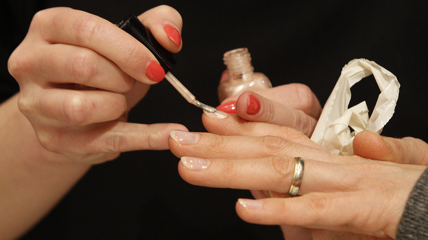 A worker paints fingernails with O2M polish at an Inglot shop in a Polish shopping center. The breathable nail polish has become a hit with Muslim women. (AP)