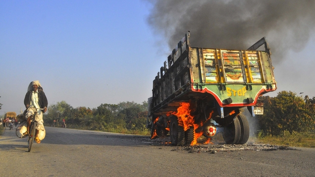 A truck burns on a street outside Bangladesh's capital, Dhaka, on Thursday. Violence erupted, and dozens have been killed, after a court sentenced an Islamist leader to the death penalty for crimes dating to the country's 1971 war of independence.