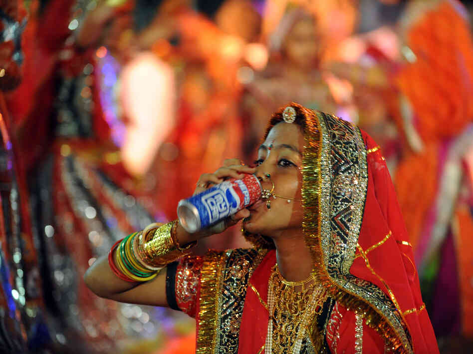 A performer drinks a soda in Ahmedabad, India in 2010. A study found that rising diabetes prevalence in countries like India is strongly tied to sugar consumption.