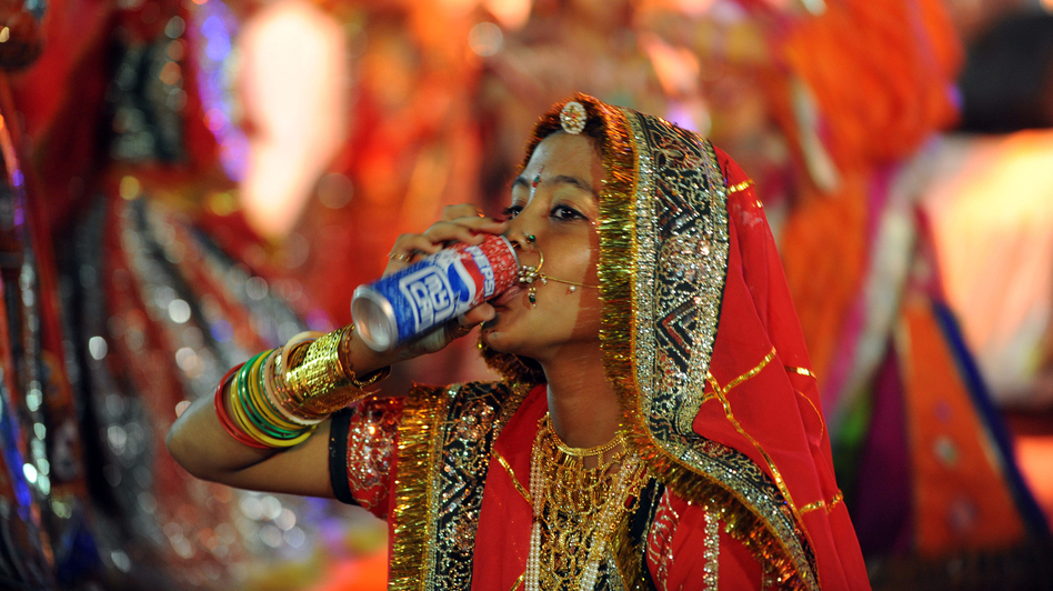 A performer drinks a soda in Ahmedabad, India in 2010. A study found that rising diabetes prevalence in countries like India is strongly tied to sugar consumption. (AFP/Getty Images)