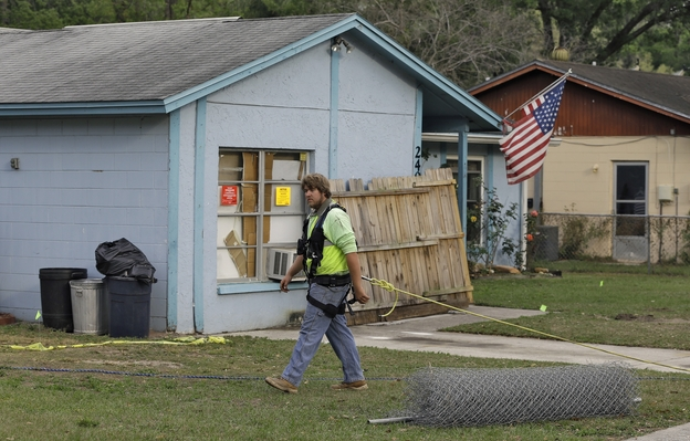 After a sinkhole swallowed a man in his bedroom in Seffner, Fla., an engineer tethered with a safety line walks in front of a home on Saturday.