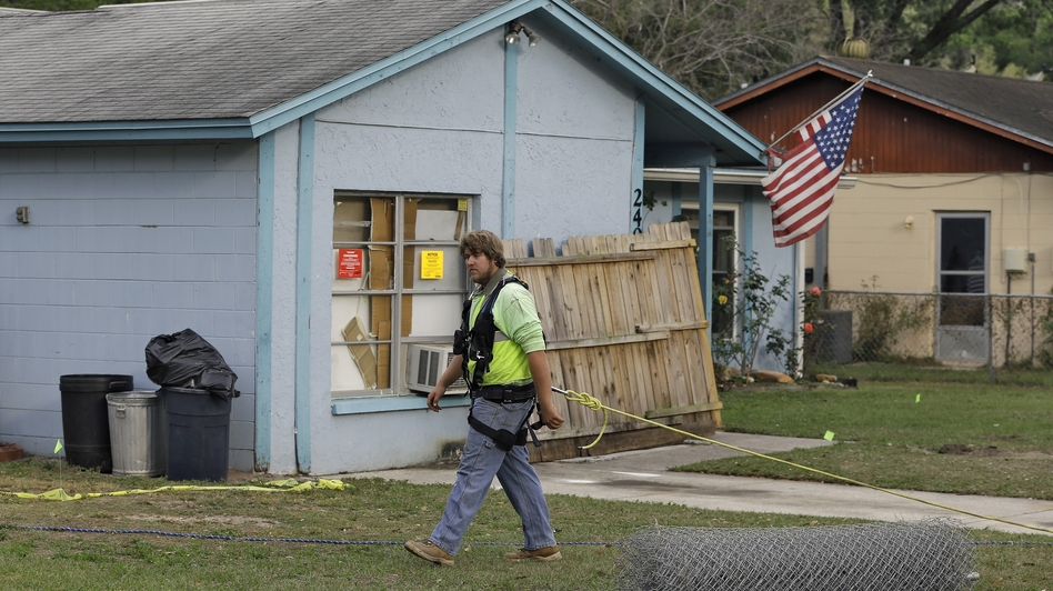 After a sinkhole swallowed a man in his bedroom in Seffner, Fla., an engineer tethered with a safety line walks in front of a home on Saturday. (AP)