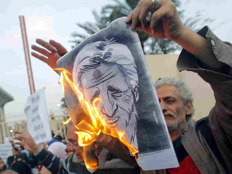 Egyptian activists burn a poster depicting Secretary of State John Kerry outside the Egyptian Foreign Ministry in Cairo on Saturday. Some accuse Kerry of supporting the Islamist government.
