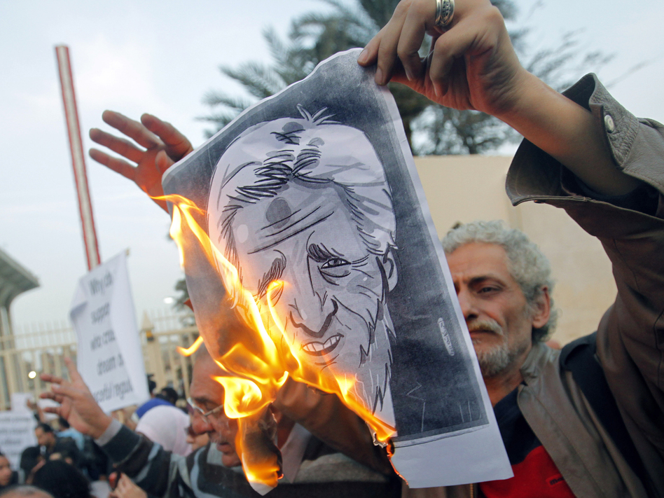 Egyptian activists burn a poster depicting Secretary of State John Kerry outside the Egyptian Foreign Ministry in Cairo on Saturday. Some accuse Kerry of supporting the Islamist government. (AP)