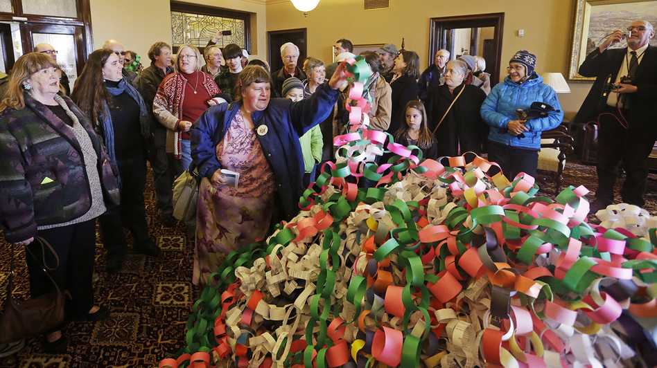 Outside the office of Utah Gov. Herbert Friday, Betsy Ogden lays paper chains on a pile symbolizing uninsured state residents who would be covered by a Medicaid expansion. (AP)