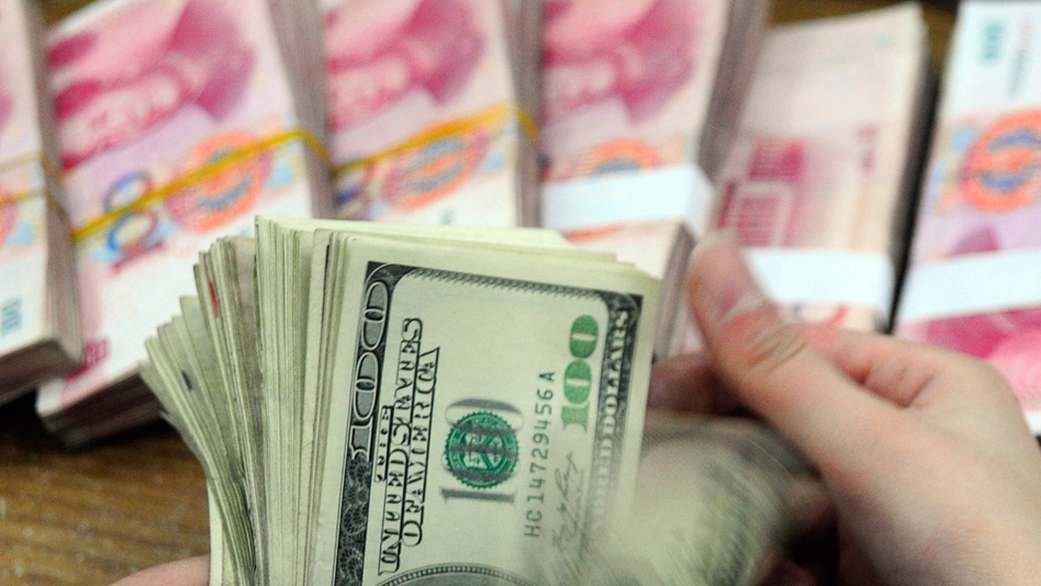 Two recent tallies of the world's richest people agree on the broad points — but not on which continent has the most billionaires. Here, U.S. dollars are counted, with Chinese yuan notes in the background. (AFP/Getty Images)