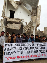 Protesters in Kafr Nabl have become famous in Syria for their posters criticizing the government. Here they pose for a photo that will instantly be posted on Facebook, in front of a building that was shelled by government forces.