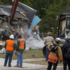 In Seffner, Fla., on Sunday, demolition crews and firefighters watched as a crane operator worked to bring down the home where a man was sucked into a sinkhole last week.