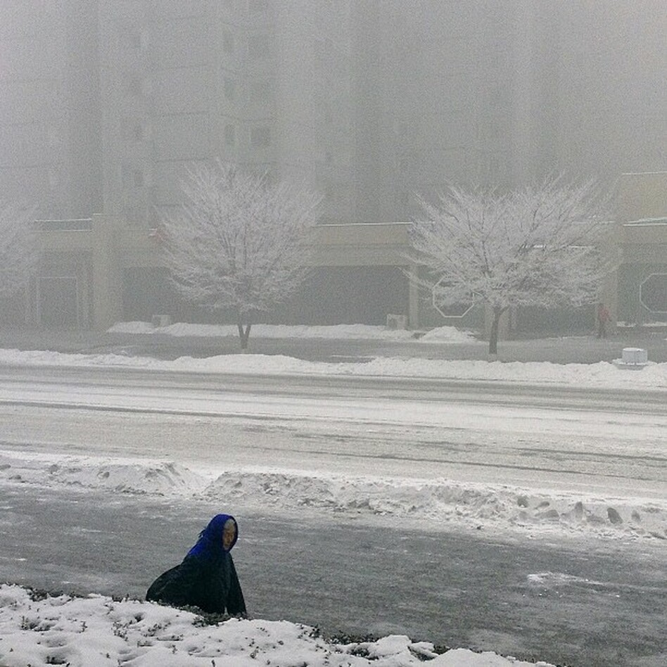 """A North Korean woman walks in snowstorm in #Pyongyang. An iPod touch photo from Jan. 13, 2013."" (AP)"