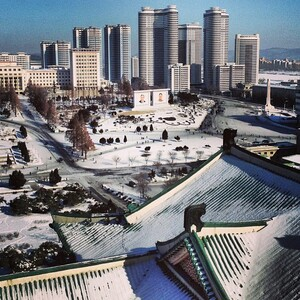 """""""This is a tourist-like view from a balcony at the Grand People's Study House. The high-rises, behind the mosaics of two Kim's, is the 3,000-unit Changjon Street apartment building complex that was completed last April. iPod touch photo from Jan. 9, 2013."""""""