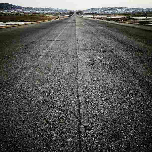 """""""The highway, heading south to #Pyongyang, North Korea. Four lanes wide and few cars to be found."""""""