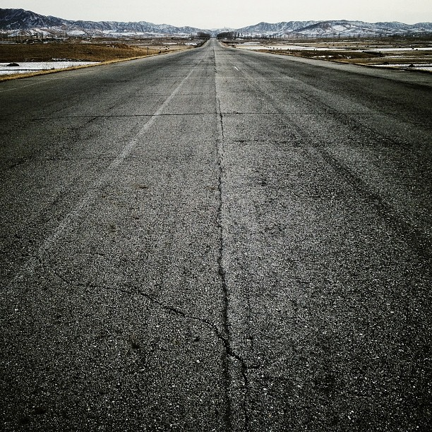 """The highway, heading south to #Pyongyang, North Korea. Four lanes wide and few cars to be found."""