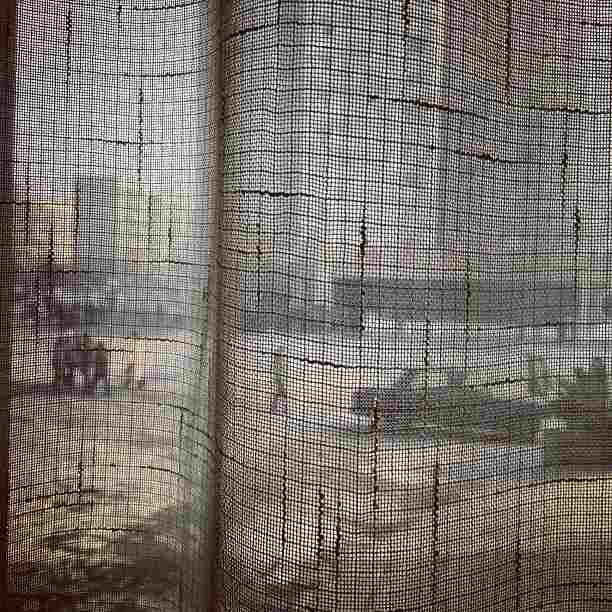 """North Koreans walk along a #Pyongyang street seen through a coffee shop window curtain on January 8, 2013."""