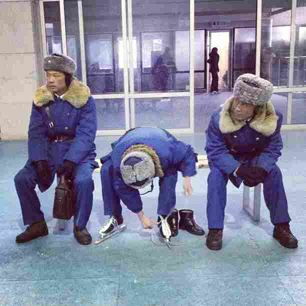 """A North Korean traffic policeman laces up his ice skates at his buddies watch at an ice skating rink in #Pyongyang."""